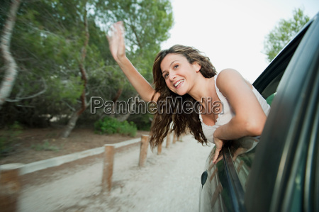young, woman, waving, from, car, window - 18660624