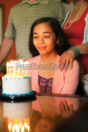 girl looking at birthday cake