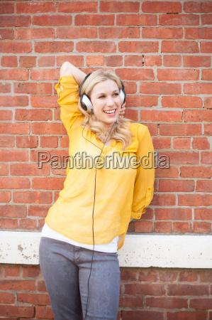 woman wearing headphones standing against brickwall