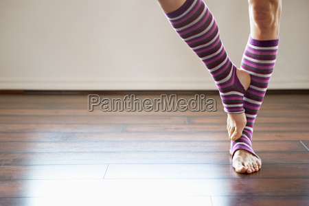 woman wearing stripey legwarmers standing on