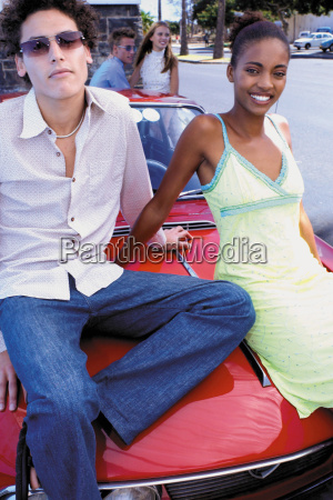 couple sitting on car bonnet