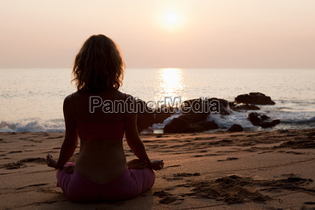 woman practicing yoga on beach at