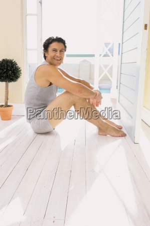 man sitting on wooden floor