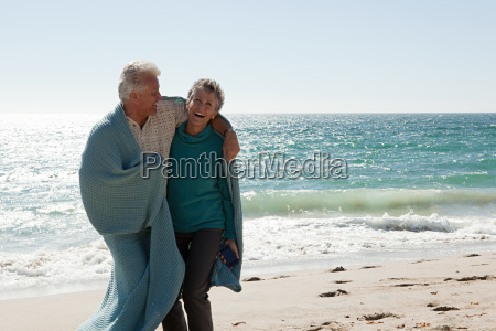 mature couple on beach wrapped in