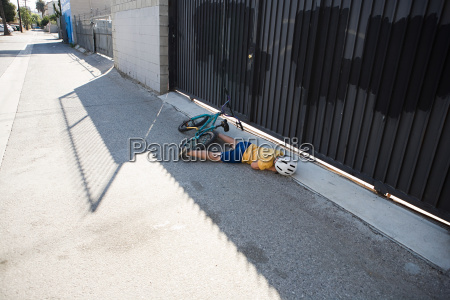 injured cyclist lying on sidewalk