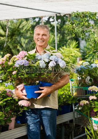 senior man with pot plants at