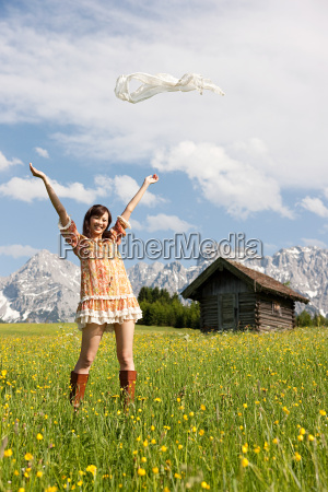 woman throwing scarf in meadow with