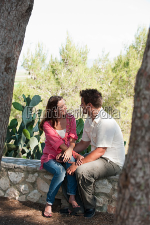young couple sitting on stone wall