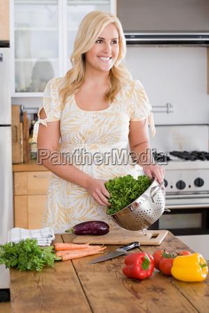 a woman preparing lettuce