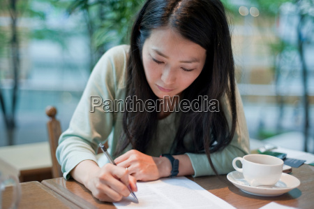 mid adult woman writing on paper