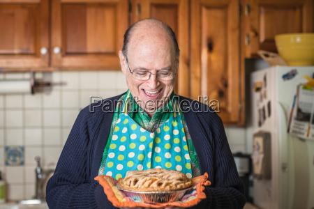 senior man holding freshly baked pie