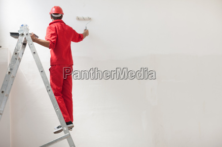 decorator on step ladder painting white