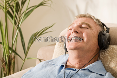 senior man relaxing with headphones on