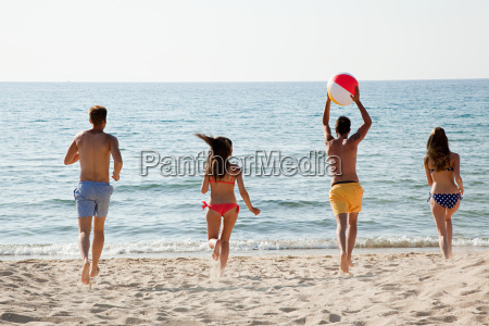 four people playing with beach ball