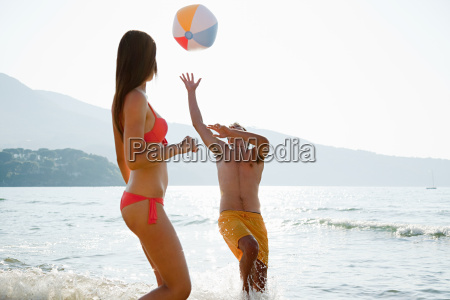 young couple playing with beach ball