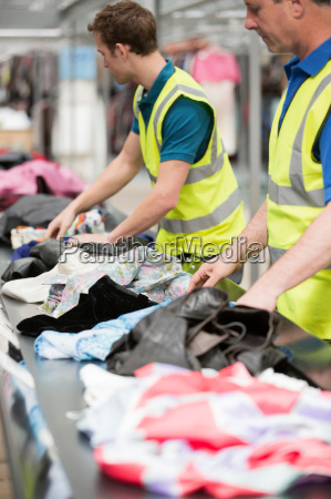 two men in warehouse sorting clothing