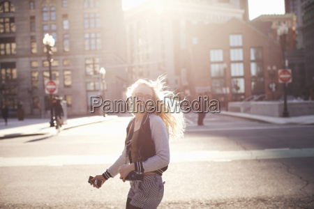 young woman walking down street in