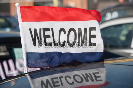 flag saying welcome at car dealership