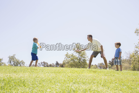 father and sons playing baseball at