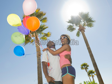 couple with bunch of balloons outdoors