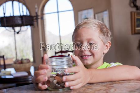 boy putting savings in glass jar