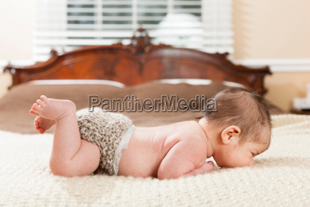 newborn infant laying on bed