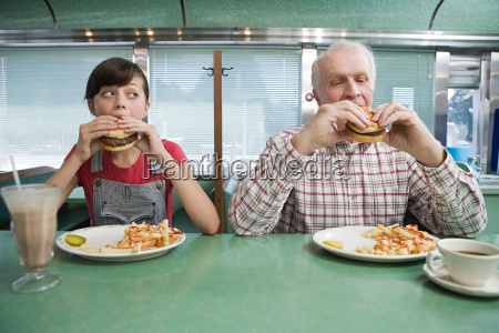 girl and old man eating burgers