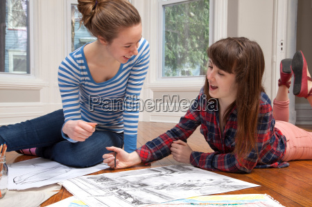 girls lying on floor drawing pictures