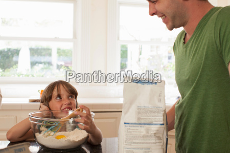 young girl baking with older brother