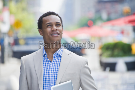 young businessman walking on city street