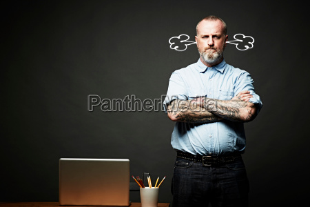 man with arms crossed fuming in