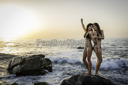 two young women standing on rock