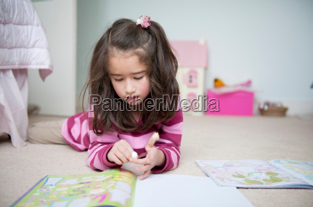 girl lying on front and reading