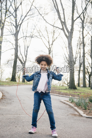 girl playing with skipping rope looking