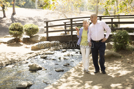 senior couple standing beside stream