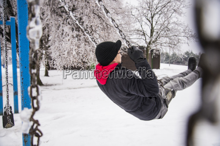 young man playing on park swing