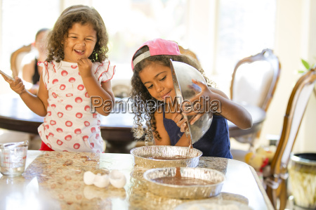 sisters pouring chocolate cake mix from
