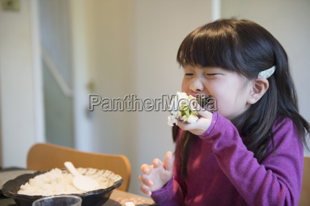 girl eating large rice parcel at