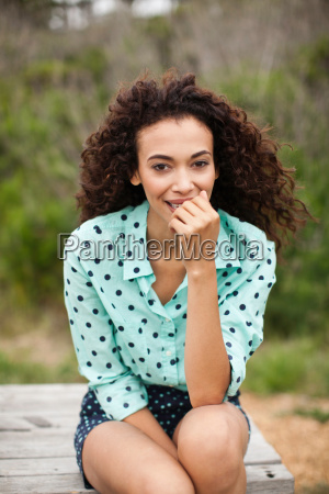 young woman sitting on picnic table