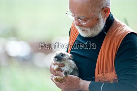 senior man holding pet rabbit