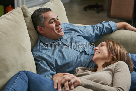 couple snuggling on sofa head in
