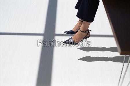 woman dangling her feet off desk