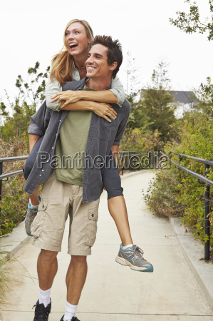couple playing piggyback ride in park
