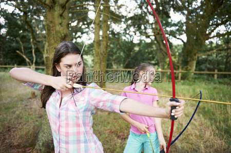girl and teenage sister practicing archery