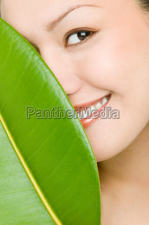 young woman hiding behind green leaf