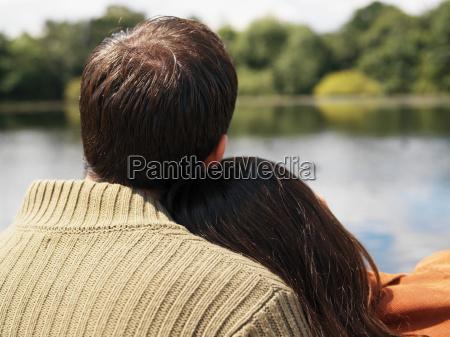 couple sitting near lake