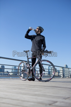 man quenching thirst behind his racing