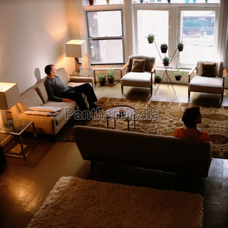 couple sitting apart in living room