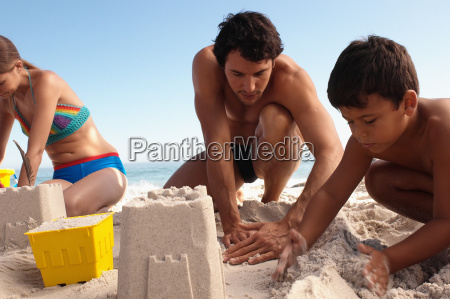 father and son building a sandcastle