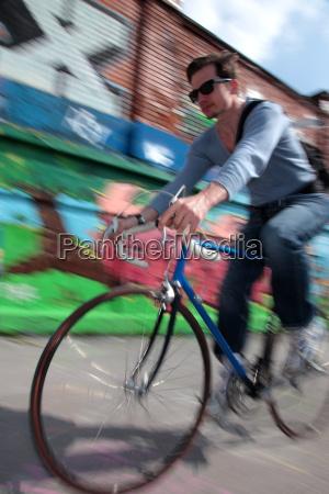 mid adult cyclist riding passed graffiti